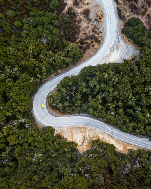 Aerial view of van on road trip on winding forest road surrounded by trees, Arthur's Pass, South Island, New Zealand.