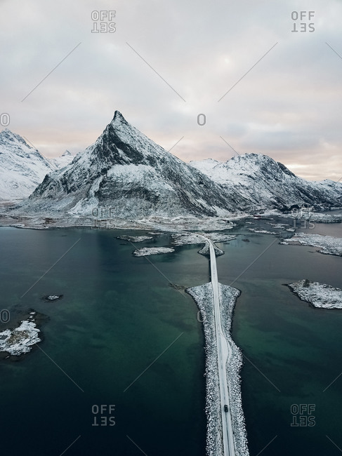 Aerial view of car driving over famous Fredvang Bridges and snowy mountains, Lofoten Islands, Northern Norway in the Arctic Circle