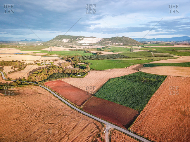 Aerial view of landscape and the different types of harvest being cultivated with a quarry in the background in Moron de la Frontera, Andalusia, Spain.