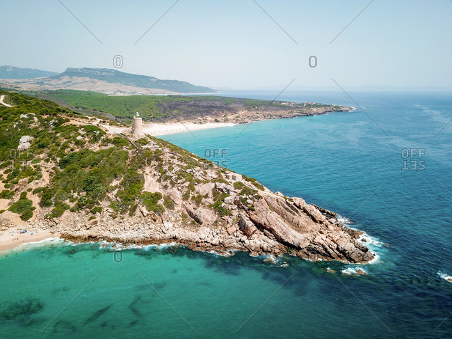 """Aerial view of the lighthouse and the rock formations near the beach of """"Playa de Entre Dos Torres"""" of the province of Cadiz, Andalusia, Spain."""