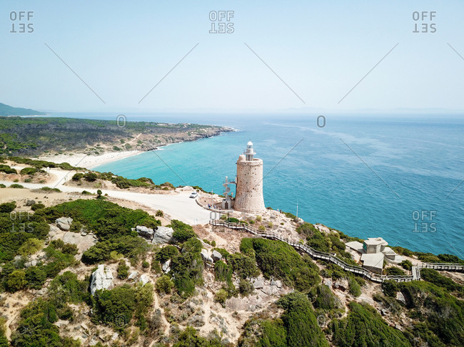 "Aerial view of a 16th century tower converted into lighthouse with the staircase going down to a scenic spot near ""Playa de Entre Dos Torres"", Andalusia, Spain."