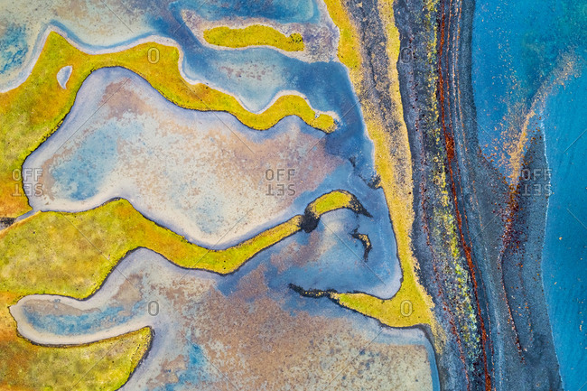 Abstract aerial view of small strips of grassland just behind a black beach, in a fjord, Westfjords, Iceland