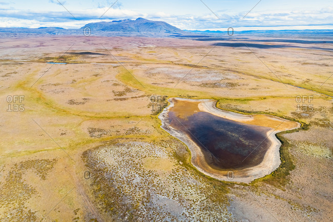 Aerial view of small partly dried out lake and mountain Blafell in the desolate highlands of Iceland