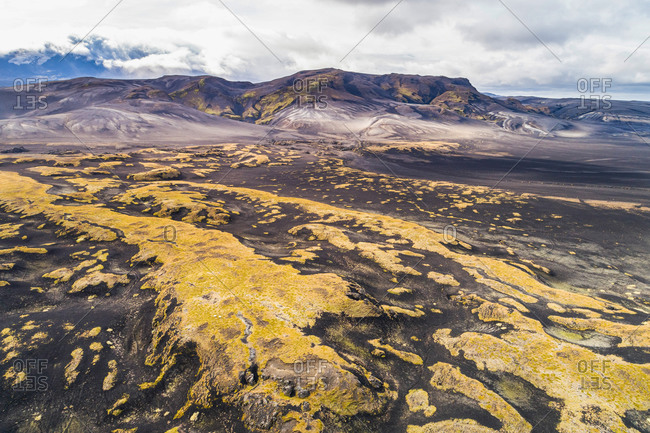 Aerial view of hilly lava field covered with mosses in front of Hekla volcano in the clouds, Iceland