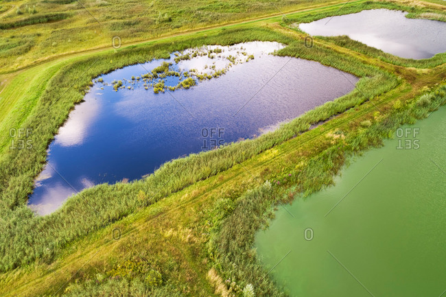 Abstract aerial view of landscaped nature reserve Volgermeerpolder, constructed on top of a former waste disposal site, with blue-green algae in one of the lakes, Noord-Holland, Netherlands