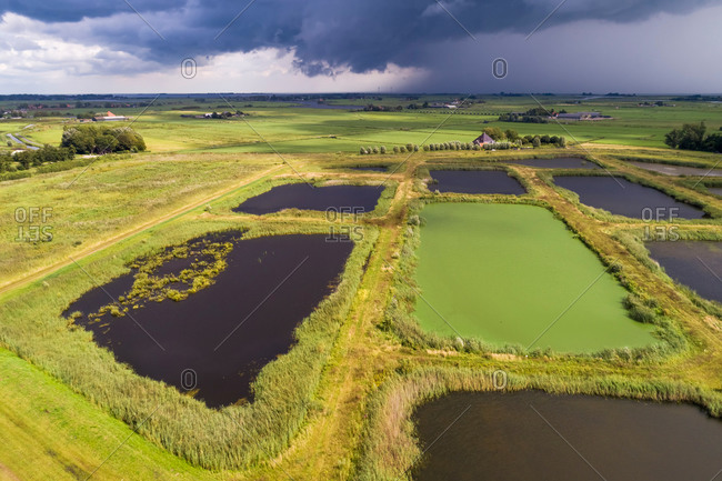 Aerial view of landscaped nature reserve Volgermeerpolder, constructed on top of a former waste disposal site, with rain shower and blue-green algae in one of the lakes, Noord-Holland, Netherlands