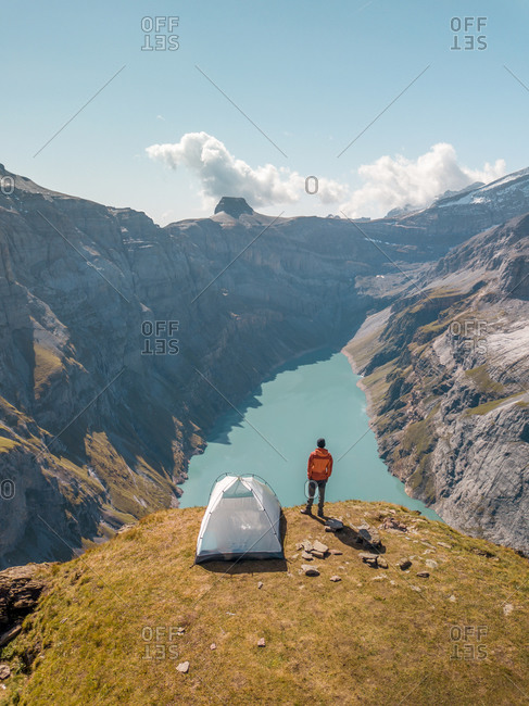 Aerial View of hiker with tent admiring view od Swiss Mountain Lake in Glarus, Switzerland.
