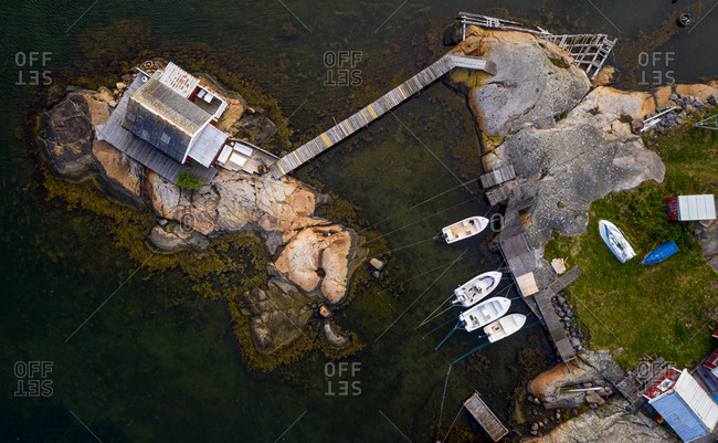 Aerial view of a cottage built on rocks and anchored boats, Gothenburg archipelago, Sweden.