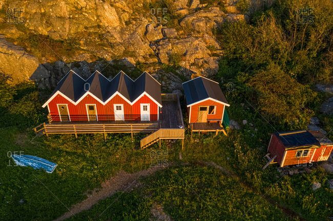 Aerial view of a small bay with red boat houses and a boat in, Gothenburg Archipelago, Sweden, Scandinavia