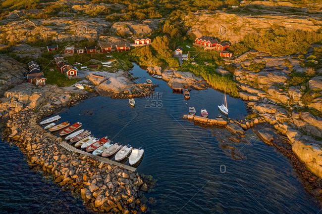 Aerial sunset view of a small rocky bay with anchord boats and red boathouses in, Gothenburg Archipelago, Sweden.