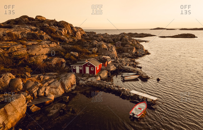 Aerial sunset view of a small rocky bay with a red cottage and anchored boats in, Gothenburg Archipelago, Sweden.