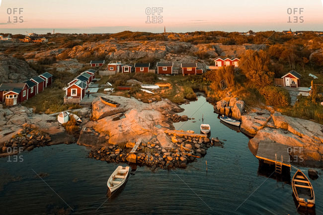 Aerial sunset view of a small rocky bay with  red boat houses  anchored boats in, Gothenburg Archipelago, Sweden.