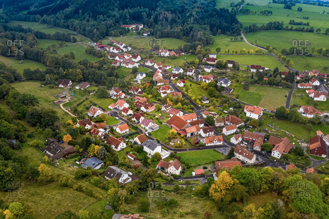 Aerial view of a village situeted in a valley of the mountain area Rhoen in autumn, Hessia, Germany.