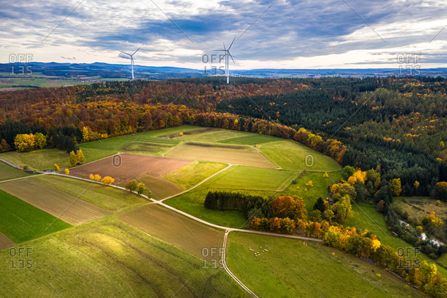 Aerial view of windmills in a forest in autumn, surrounded by fields,  Hessia, Germany.