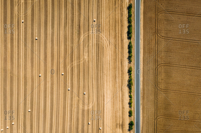 Abstract aerial view of straw bales in field divided by a road in Schernberg, Germany.
