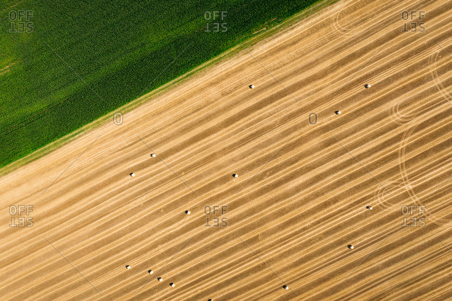 Abstract aerial view of straw bales in field next to a green grass field in Schernberg, Germany.