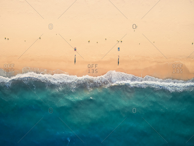 Aerial view of two persons keeping a social distancing while they soaking the sun on a beach in the late afternoon near Sant'Andrea Apostolo dello Ionio, Calabria, Italy.