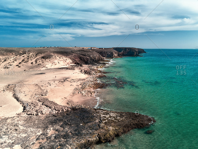 Aerial view of the solitary beach with a man walking along the shoreline in Playa del Pozo, Lanzarote, Spain.