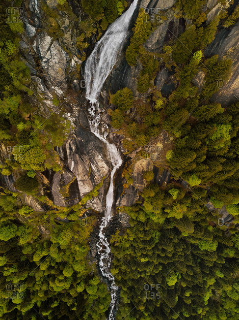 Aerial view of a steep majestic waterfall hidden by the forest in Val di Mello, Lombardy, Italy.