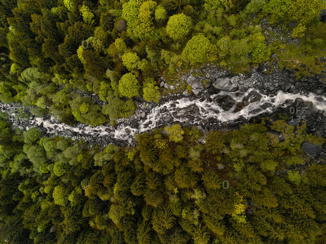 Aerial view of a mountain stream rushing at speed through a lush forest in Val di Mello, Lombardy, Italy.