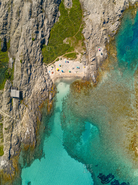 Aerial view of an amazing beach in front of a little cove with turquoise waters and many colorful parasols in Stintino, Sardinia, Italy.