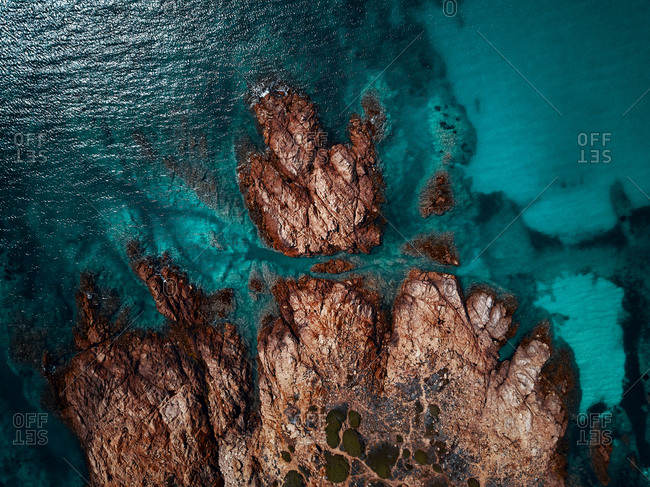 Aerial view of a reddish remote cliff surrounded by spectacular turquoise waters near Isola Rossa, Sardinia, Italy.