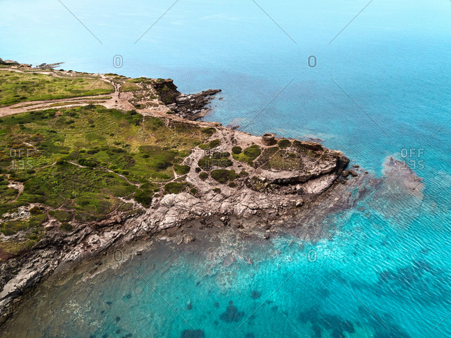 Aerial view of a spectacular cove enclosed by a cliff with an ancient watch tower from the Middle Age in Porto Ferro, Sardinia, Italy.