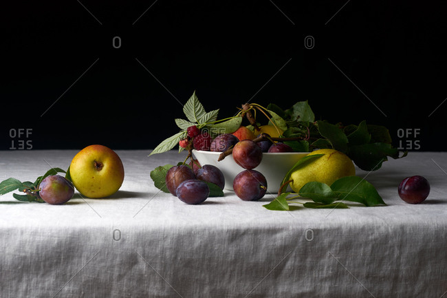 Still life with fresh organic fruits from the garden: plums, pears and apples on white textile background