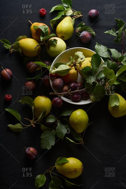 Overhead image of organic fruits arranged on black background