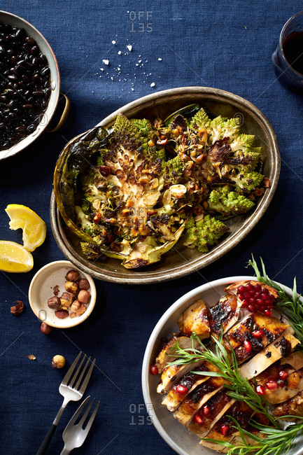 Overhead image of healthy dinner with roasted chicken, romanesco broccoli steaks and cooked black beans with herbs.