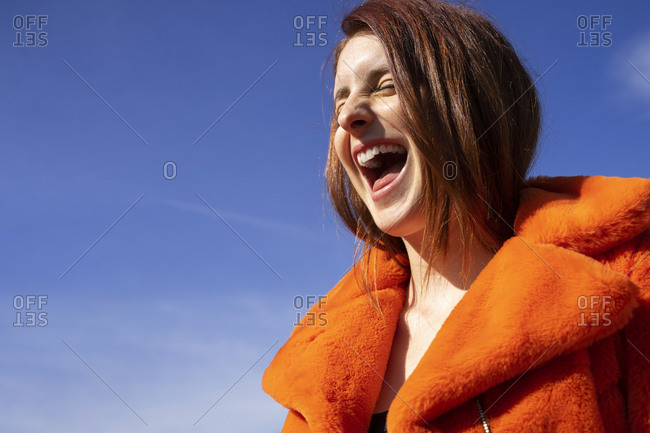 Young woman with mouth open standing against clear sky