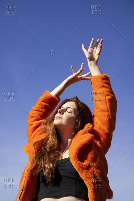 Young woman with eyes closed and hand raised standing against clear sky