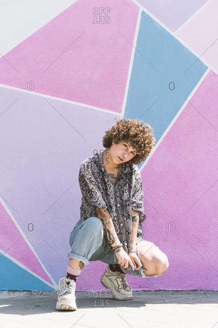 Young woman crouching against multi colored wall