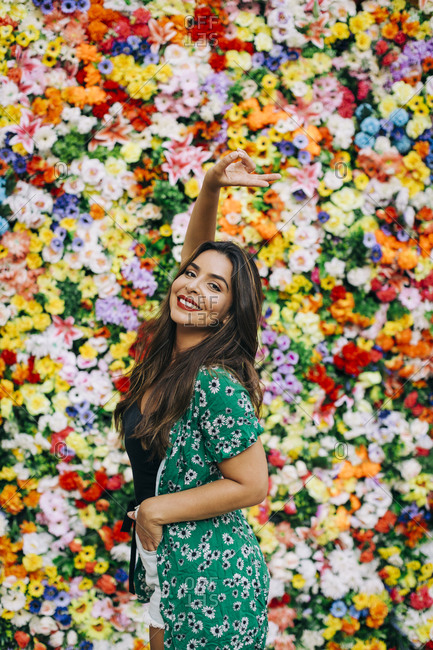 Beautiful woman showing peace sign while standing against colorful flowers