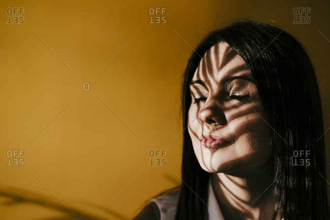 Mid adult woman with leaf shadow on face against yellow wall