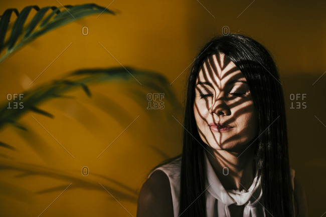 Woman with leaf shadow on face against yellow wall