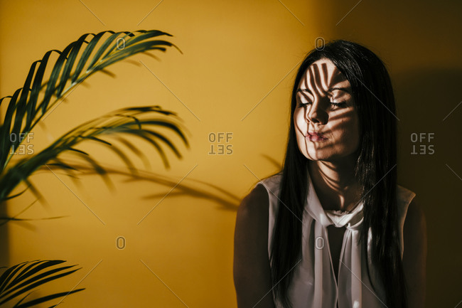 Contemplating woman with leaf shadow on face against yellow wall