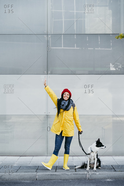 Woman with arms raised standing with dog on footpath during autumn