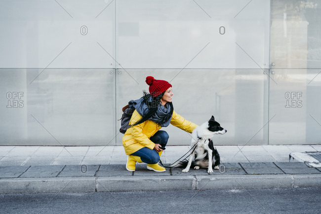 Woman looking away while crouching with dog on footpath