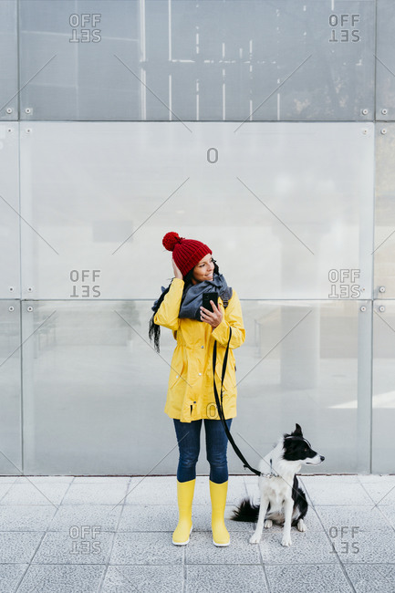 Smiling woman looking away while using smart phone standing with dog on footpath against wall