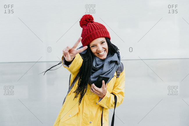 Woman smiling while doing peace sign holding smart phone while standing against wall