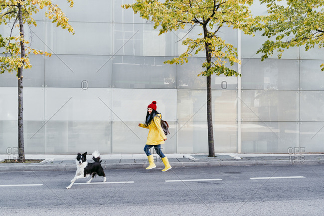 Happy woman running on street behind dog during autumn