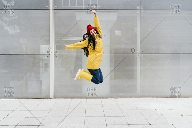 Cheerful woman jumping with arms raised on footpath against building exterior