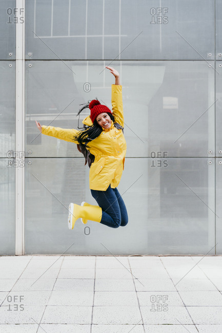 Happy woman jumping with hand raised on footpath against building exterior