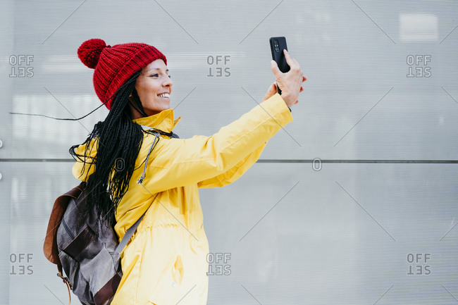Woman taking selfie on smart phone while standing by gray wall