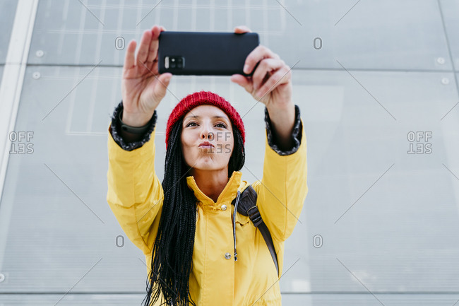 Woman taking selfie on smart phone while standing against gray wall