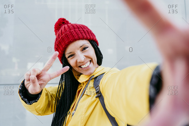 Smiling woman doing peace sign while standing against gray wall during autumn