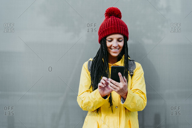 Smiling woman using smart phone standing against gray wall during autumn