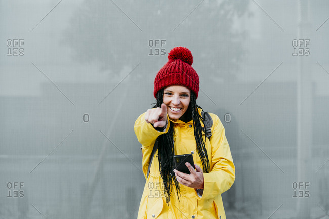 Woman pointing while holding smart phone standing against gray wall