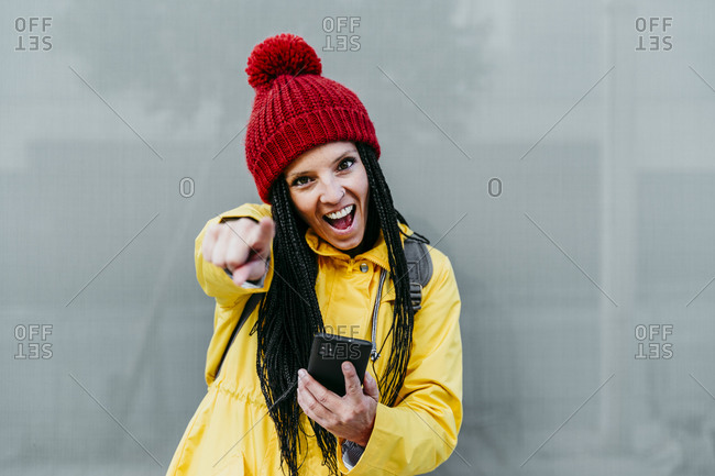 Woman pointing with mouth open while holding smart phone standing against gray wall